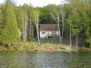 Our little lake house this spring, viewed during our first boat ride of the season.